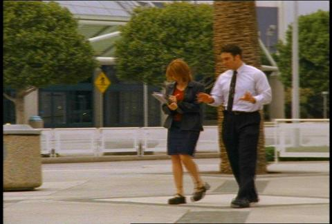 Business Man and Woman Walk Outdoor Talking