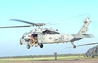 U.S. Navy and Air Force Crews Load Rescue Equipment Onto Helos